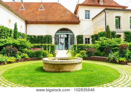 fountain in a courtyard with white residence
