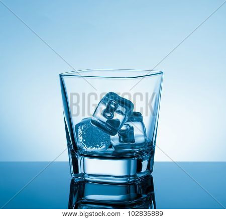 Empty Glass Of Whiskey On Black Table With Reflection And Ice On Light Blue Tint Background