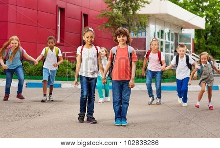 Rows of kids with rucksacks near school walking
