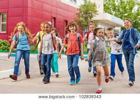 Happy kids with rucksacks walking holding hands