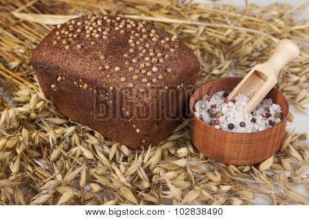 Loaf of homemade bread with black mustard seeds on a table with spikelets of rye and salt shaker of salt.