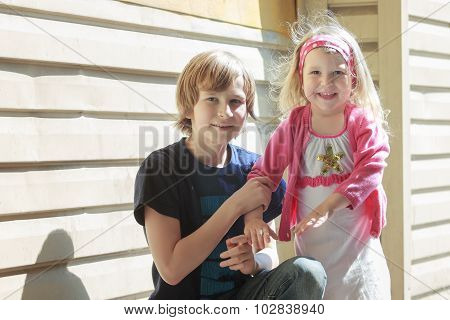 Outdoors portrait of sibling children at light yellow corrugated galvanized iron building wall