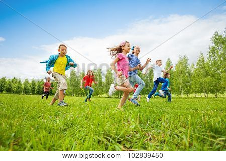 Children are running through green field together