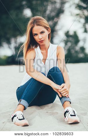 Young Woman Sitting On The Beach Sand And Posing