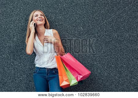 Happy Young Woman Talking On The Phone After Shopping