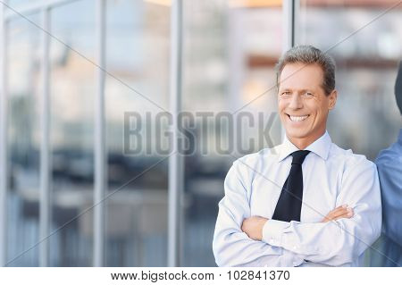 Nice businessman standing near office building