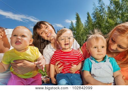 Three happy women holding cute toddlers in park