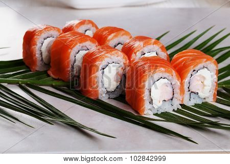 Philadelphia roll with shrimp sushi food on a tropical palm leaves to the menu
