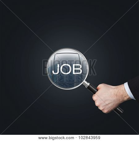 A Hand Holds A Magnifying Glass With The Word 'job'. The Concept Of The Searching Of The Job. Dark B