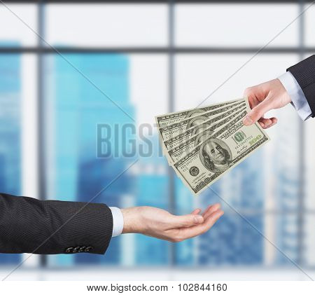 Two Hands, Money Transferring Process. Dollar Bills. Business City View On The Background Form The P