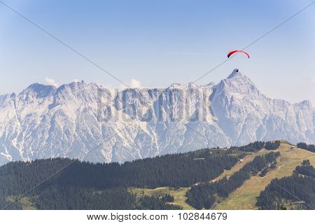 Paraglider Flyes Over Mountains In Alps, Austria