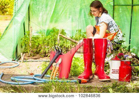 Female Farmer And Gardening Tools In Garden