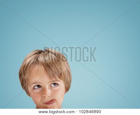 Boy with tongue out licking his lips looking up at copy space for a message or product placement