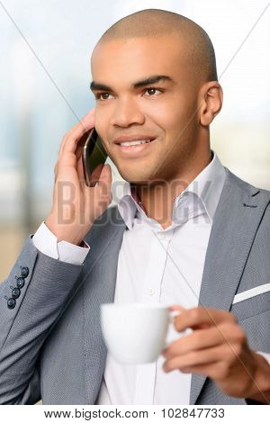 Pleasant businessman drinking coffee
