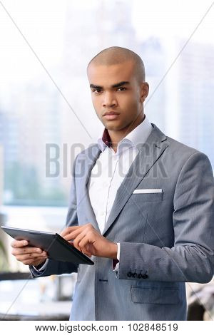 Handsome businessman holding laptop