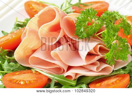 detail of fresh arugula leaves with sliced ham and halved tomatoes