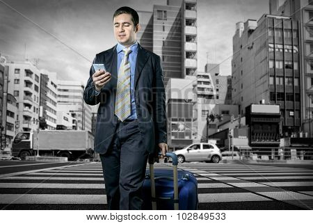 Man with baggage speaking by phone on the crossroad