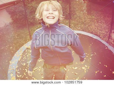 Smiling boy jumping on a trampoline, Instagram filter effect.