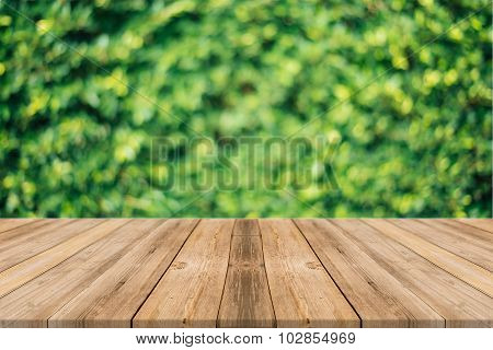 Wooden board empty table blur trees in forest - can be used for display or montage your products.