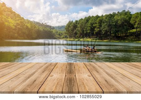Wooden Board Empty Table blur lake in forest - can be used for display or montage your products.