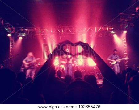 a crowd of people at a concert with one making a heart shape with slight grain toned with a retro vintage instagram filter effect app or action