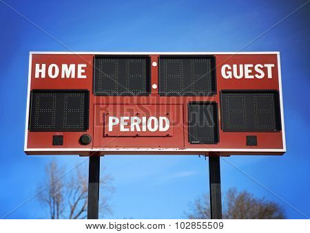 background of a scoreboard with home and guests written on it in front of a blue sky on a sunny summer day