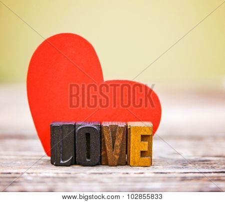 a paper heart with some wooden block letters on a wooden background