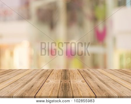Wooden Board Empty Table blur store in mall - can be used for display or montage your products.