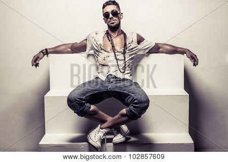 Full Length Portrait of Young Man Wearing Sunglasses and Torn Shirt Leaning Back with Open Arms on Studio Steps