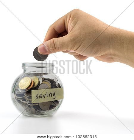 Hand Putting Coin Into Glass Container With  Saving Label On White Background. Selective Focus.