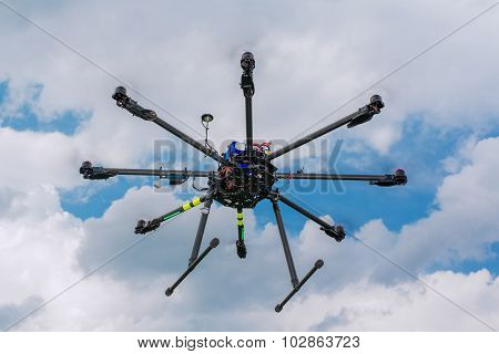 Multicopter in flight on sky clouds background