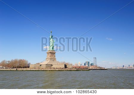 Statue of Liberty on Liberty Island and New York City Manhattan downtown skyline with skyscrapers and blue sky