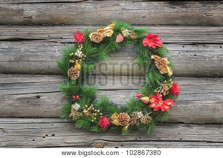 Green with red and gold Christmas conifer wreath at old log cabin wall background
