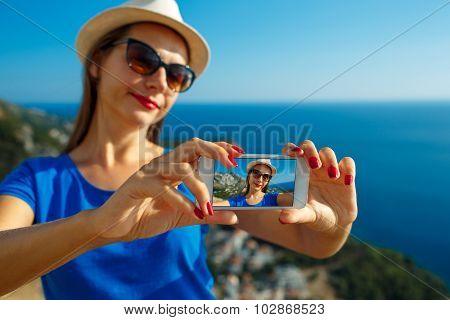 Girl In The Hat Making Selfie By The Smartphone On The Background Of Sea Coast,  Adriatic Sea, Monte