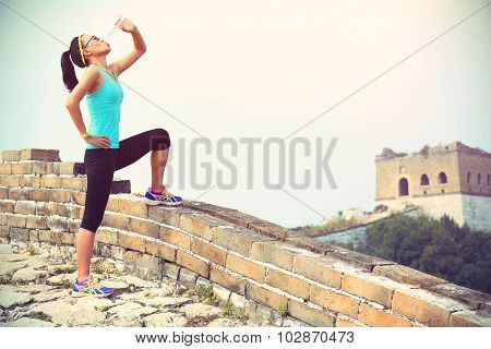 woman runner athlete drinking water after run on chinese great wall.