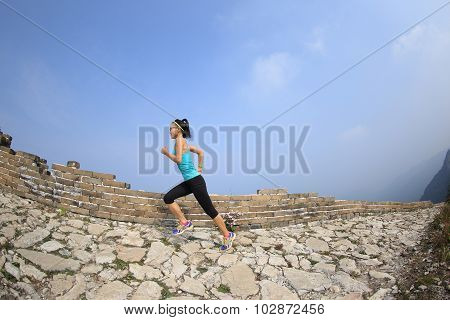woman runner athlete running on trail at chinese great wall .