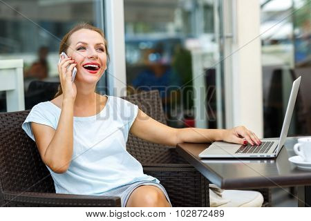 Attractive Woman Sitting In A Cafe With A Laptop And Talking On The Cell Phone
