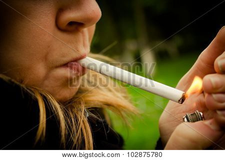 Smoking in the middle of the nature. Inhaling toxic air while surrounded by natural fresh air
