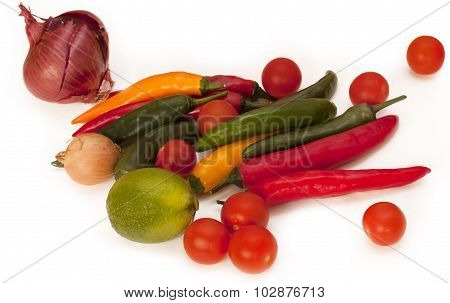 A heap of bright red, yellow and green chili peppers and cherry tomatoes with a lime and onions
