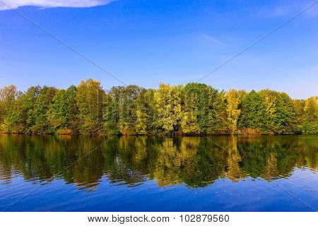 Landscape With River And Multicolored Trees In Autumn Time