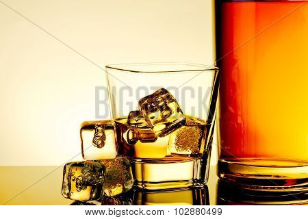 Glass Of Whiskey With Ice Cubes Near Bottle And Ice Cubes On Table With Reflection, Warm Tint Atmosp