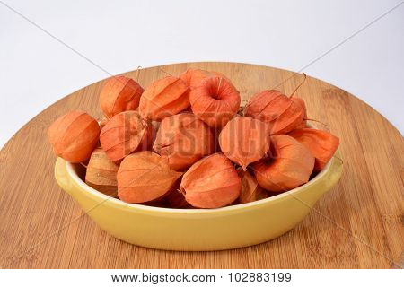 Red Physalis In A Bowl  Over White