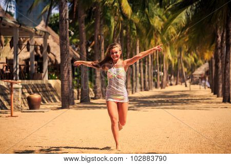 Blonde Girl In Lace Runs Barefoot Between Palms On Beach