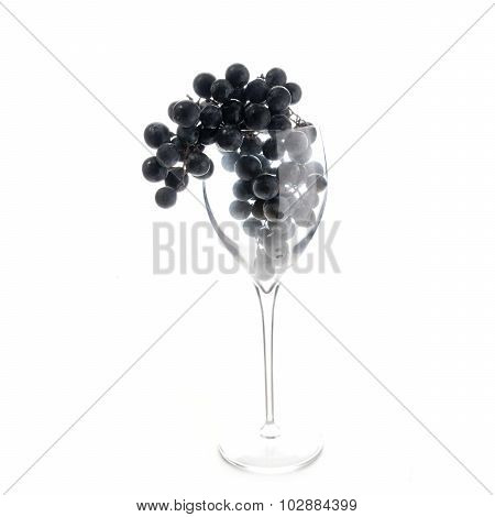 Grapes In Red Wine Glass Hanging Over Isolated Against White
