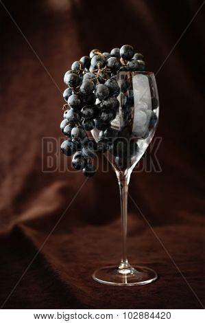 Black Grapes In Wine Glass Hanging Over Against Brown Background