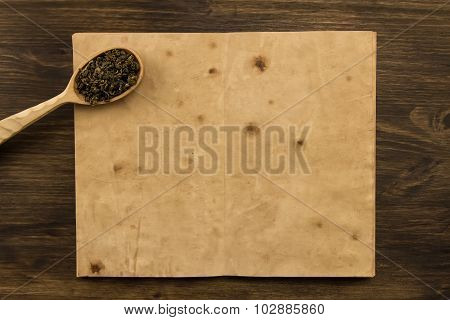 Oolong Tea Spoon In The Old Blank Open Book On Wooden Background. Menu, Recipe, Mock Up