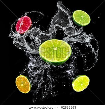 Fresh limes, lemon, orange and grapefruit with a water splash isolated on a black background