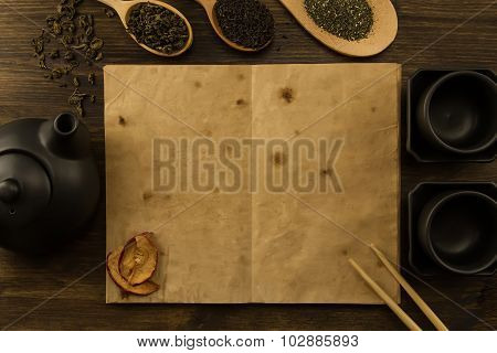Black Teapot, Two Cups, A Collection Of Tea, Dried Apples, Old Blank Open Book On Wooden Background.