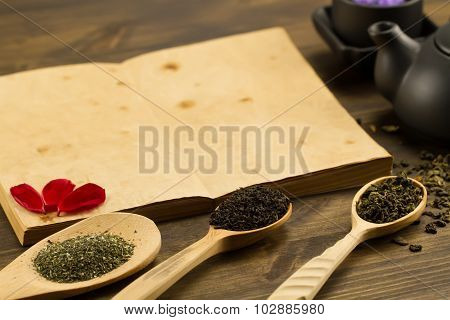 Black Teapot, Cups, Tea Collection, Flowers, Old Blank Open Book On Wooden Background. Menu, Recipe,