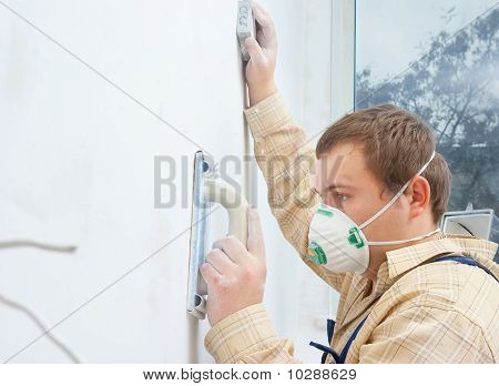 young builder polishing wall
